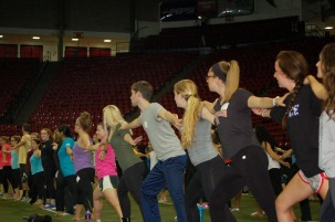 Participants in the Yoga World Record event hit their warrior pose, Tuesday, Oct. 14, 2014, in Cole Field House.