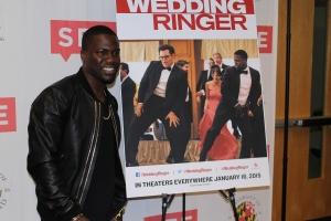 "Comedian Kevin Hart poses beside ""The Wedding Ringer"" advertisement November 1, 2014. (Lauryn Froneberger/ Pulsefeedz)"
