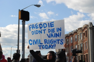 """Protestor holds sign up high """"Freddie didn't die in vain! Civil Rights Today!"""""""