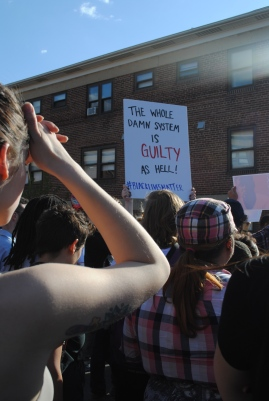 """Protestor holds sign """"The whole damn system is guilty as hell #blacklivesmatter."""""""