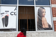 Young girl, not in school because of closings, looks inside of looted beauty store.