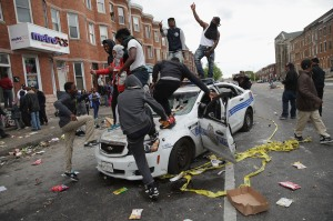 BALTIMORE, MD - APRIL 27: Demonstrators climb on a destroyed Baltimore Police car in the street near the corner of Pennsylvania and North avenues during violent protests following the funeral of Freddie Gray April 27, 2015 in Baltimore, Maryland. Gray, 25, who was arrested for possessing a switch blade knife April 12 outside the Gilmor Homes housing project on Baltimore's west side. According to his attorney, Gray died a week later in the hospital from a severe spinal cord injury he received while in police custody. (Photo by Chip Somodevilla/Getty Images)