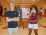 Jordan Greenwald and Maya Dawit stand at the front of Smith School with a Meta Cartel hat